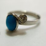 This unique engagement ring  made in platinum holds an oval turquoise and a small round off set diamond. Price guide £900. 4 of 4.